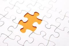 Orange puzzle piece missing. White puzzle piece missing on orange background royalty free stock photo