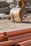 Orange pvc pipes. On construction site, excavator bucket in background royalty free stock images