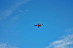 Orange quadcopter auf dem blauen Himmel Lizenzfreie Stockfotografie