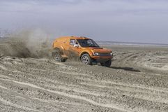 Orange race car on the beach. At full speed Royalty Free Stock Photography
