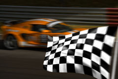 Orange racing car and chequered flag. Orange racing car passing chequered flag with motion blur royalty free stock photos