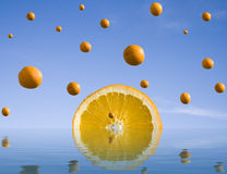 Orange rain. Falling oranges on the background of clear blue sky and water. Abstract background Stock Photography