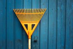 Orange rake leaning at blue wooden wall. Closeup of orange rake leaning at blue wooden wall royalty free stock image