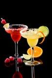 Orange and Raspberry margaritas - Most popular co. Orange and Raspberry margaritas in chilled glass over black background on reflection surface, garnished slice stock images