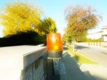 Orange Raumwarnungslicht gelegen auf einem Ziegelsteinzaunposten Wechselsprechanlagenwohngebäude am Eingang auf ein privates Schu lizenzfreies stockbild