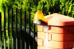 Orange Raumwarnungslicht gelegen auf einem Ziegelsteinzaunposten Wechselsprechanlagenwohngebäude am Eingang auf ein privates Schu stockfotos