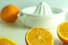 Orange ready for a tasty juice for breakfast. Oranges ready for a tasty juice on a white table and background Stock Image