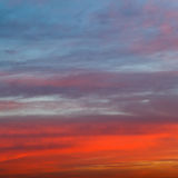Orange red and blue early morning sunrise sky Stock Photos