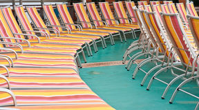 Orange and Red Chaise Lounges on Green Deck. Rows of colorful chaise lounges on a green deck stock photos
