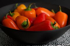 Orange and Red Chili Peppers in Black Bowl Stock Photography
