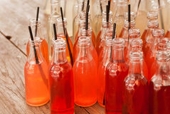 Orange and red color refreshing drinks inside the small bottles with tubes on a wooden table in a outdoor cafe. Stock Photo