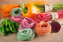 Orange, red and green raw italian pasta with its natural vegetab Stock Photography