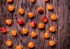 Orange, red heart shaped pills or candy on vintage Stock Images