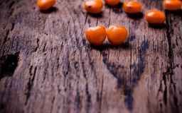 Orange, red heart shaped pills or candy on vintage. Valentines day background. Orange, red heart shaped pills or candy on  vintage wooden background. Copy space Royalty Free Stock Photography
