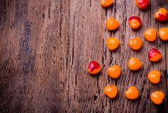 Orange, red heart shaped pills or candy on vintage Royalty Free Stock Images