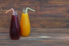 Orange and Red Juices in Bottles on rustic Wooden Background. Copy space for Text. Orange and Red Juices in Bottles on rustic Wooden Background. Copy space Royalty Free Stock Images