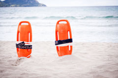 Orange red life buoy in sand on beach at the sea Royalty Free Stock Photo