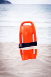Orange red life buoy in sand on beach at the sea Stock Image