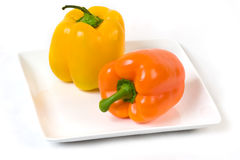 Orange and red peppers. Orange and red sweet peppers on white plate Stock Images