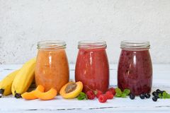 Orange, red and purple smoothies of fresh ingredients - bananas, apricots, raspberries and blueberries on a light background. Heal. Thy food concept. Vegetarian Royalty Free Stock Photo