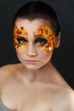 Orange and Red Rhinestones on a Girl Face. Portrait of a girl with an original make-up. Beauty close-up with orange and red rhinestones on a face of the model Royalty Free Stock Photography