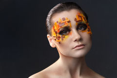 Orange and Red Rhinestones on a Girl Face. Portrait of a girl with an original make-up. Beauty close-up with orange and red rhinestones on a face of the model Stock Image