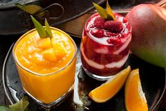 Orange and Red smoothie and orange fruits with green leaves on d stock photos