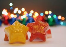Star soaps. Orange and red soaps in shape of a star with golden details,christmas light in background Royalty Free Stock Images
