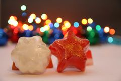 Star soaps. Orange and red soaps in shape of a star with golden details,christmas light in background Royalty Free Stock Photo