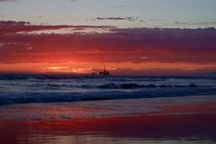 Sunset at the beach with oil rig. Orange red sunset at the beach with oil rigs and a cargo ship in the distance off the coast of Huntington Beach California stock photo