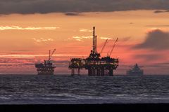 Sunset at the beach with oil rig. Orange red sunset at the beach with oil rigs and a cargo ship in the distance off the coast of Huntington Beach California royalty free stock photo