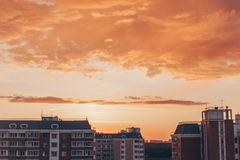Orange-red sunset with clouds with residential buildings. Orange-red sunset with clouds in summer with residential buildings stock images