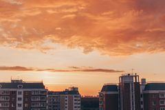 Orange-red sunset with clouds with residential buildings. Orange-red sunset with clouds in summer with residential buildings royalty free stock photography