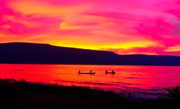 Orange red sunset over Lake Tanganyika. There are two makoros canoe with fishermen in the water. The orange red sky is reflected in the water. Location Malawi stock photography