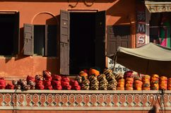 Orange and red turbans. Red brick colored house and turbans in a comercial house in Jaipur Royalty Free Stock Photography