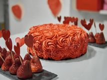 Orange red whipping cream cake decorated with silver edible pearls, black pads with strawberry decorated paper red hearts on white royalty free stock images