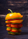 Orange red yellow and green paprika. Peppers with slice over stone table Stock Images