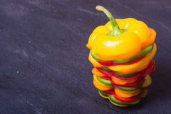 Orange red yellow and green paprika. Peppers with slice over stone table Royalty Free Stock Photography
