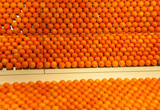 Orange reflections. Mirrored images of the shelves of oranges below Royalty Free Stock Photo