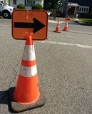 Orange Reflective Traffic Safety Cones with Arrows. Arrows attached to orange cones advise motorists to turn to avoid utility work taking place on the westbound Royalty Free Stock Image