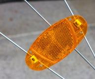 Orange reflector on bicycle wheel spokes Royalty Free Stock Images