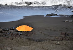 Orange Regenschirm auf dem Strand Stockfotografie