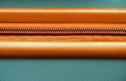 Orange Reißverschluss auf einem Kofferhintergrund Stockfotografie