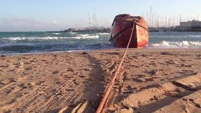 Orange rescue boat on the Mediterranean sea shore with stormy waves and harbour on the backgroud. stock footage