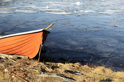Orange rescue boat on the shore of a frozen lake Royalty Free Stock Images