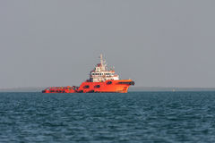 Orange rescue ship sails across the bay at sunset. Stock Photography