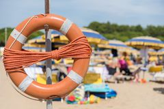 Lifebuoy on the beach. Orange rescue tire on a bathing beach - closeup Stock Photography