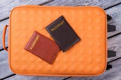 Orange resväska och två passposrts på arkivbild