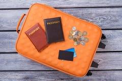 Orange resväska, två pass och mynt royaltyfria foton