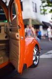 Orange retro tappningbil med bilshow för öppen dörr Arkivfoto